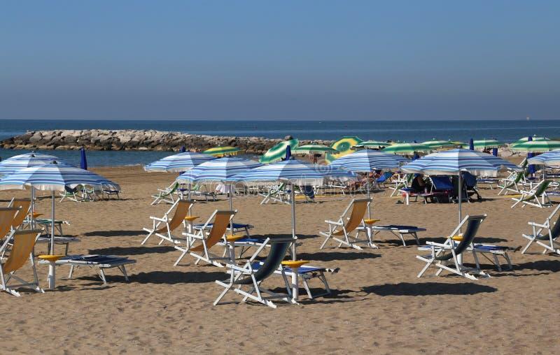 遮阳伞和轻便折叠躺椅在洒满阳光的海滩在夏天 图库摄影