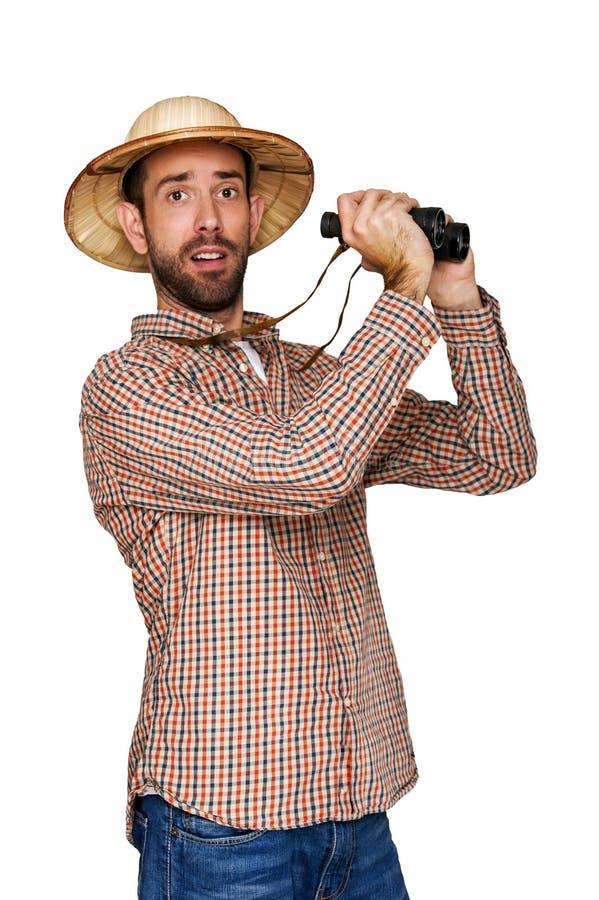 头戴遮阳帽的年轻人看通过一台双筒望远镜有一个惊奇的表示的 图库摄影