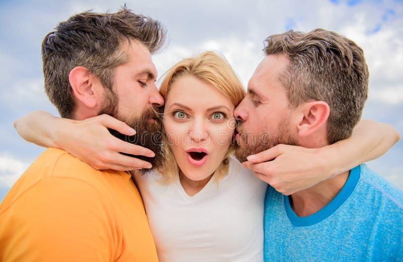 避免朋友区域的最后指南 人亲吻同样女孩面颊 夫人享受联系两位钦佩者 人坠入爱河 库存照片