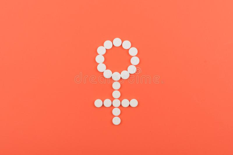 避孕药,口服避孕药,荷尔蒙方法 以女性金星标志的形式白色药片在珊瑚背景 免版税库存图片