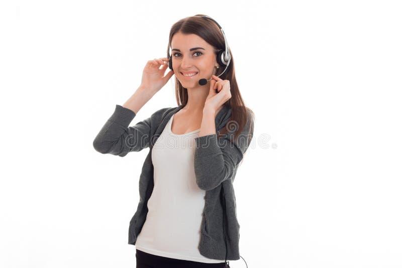 避开的耳机和灰色夹克的美丽的女孩和在面孔附近保留手话筒 免版税图库摄影