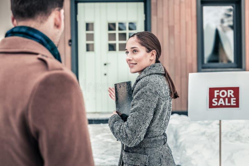 邀请不动产的房地产经纪商她的客户进入房子和看它 库存照片