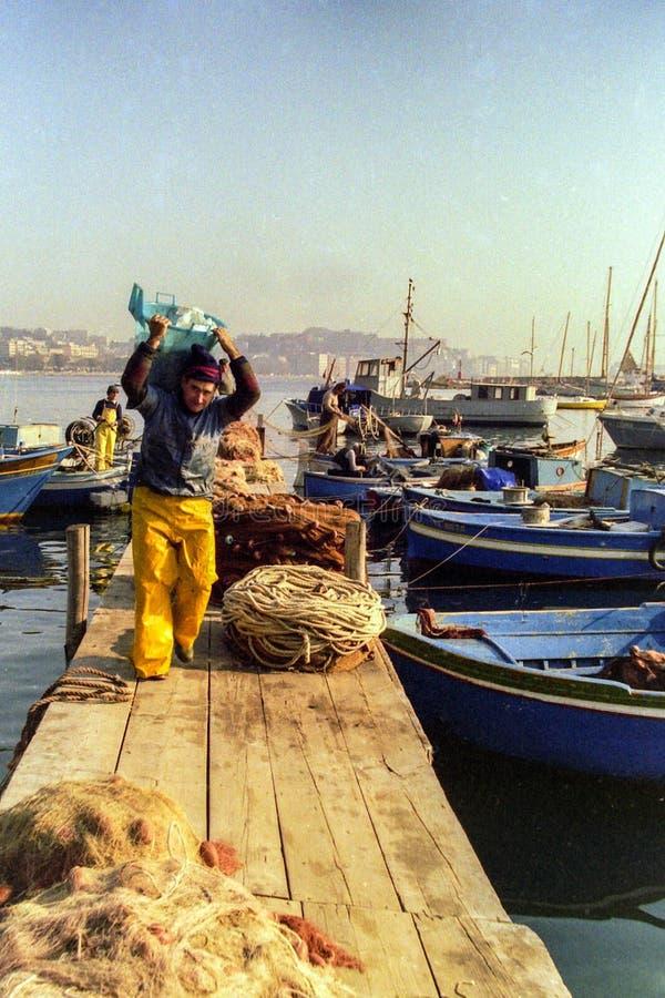 那不勒斯,意大利,1988年-渔夫在一个钓鱼日结束时停泊他们的在Mergellina港的小船并且安置他们的 库存图片