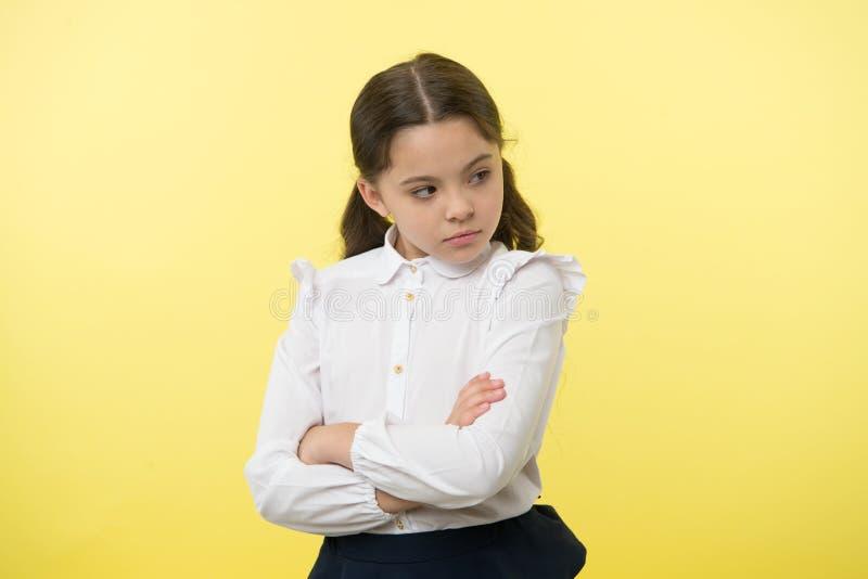 那不是公平的 学生不同意标记 女孩严肃的面孔被触犯的黄色背景 严密孩子不快乐的神色 库存图片