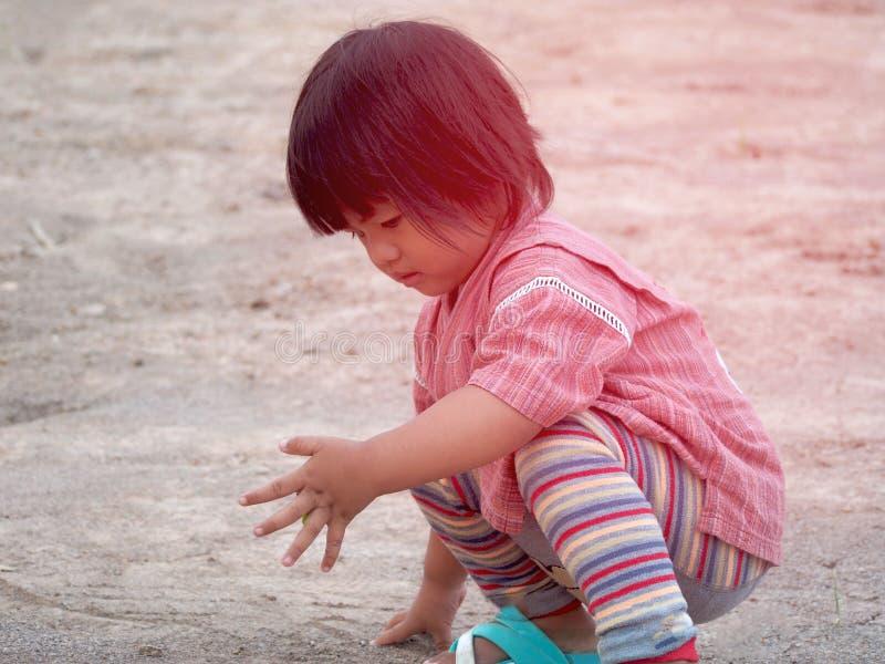 那女孩穿着绿色衬衫 在草地上玩耍 库存图片