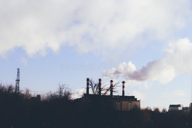 那里冬天寒冷在居民住房加热 工业管子 烟来自它 图库摄影