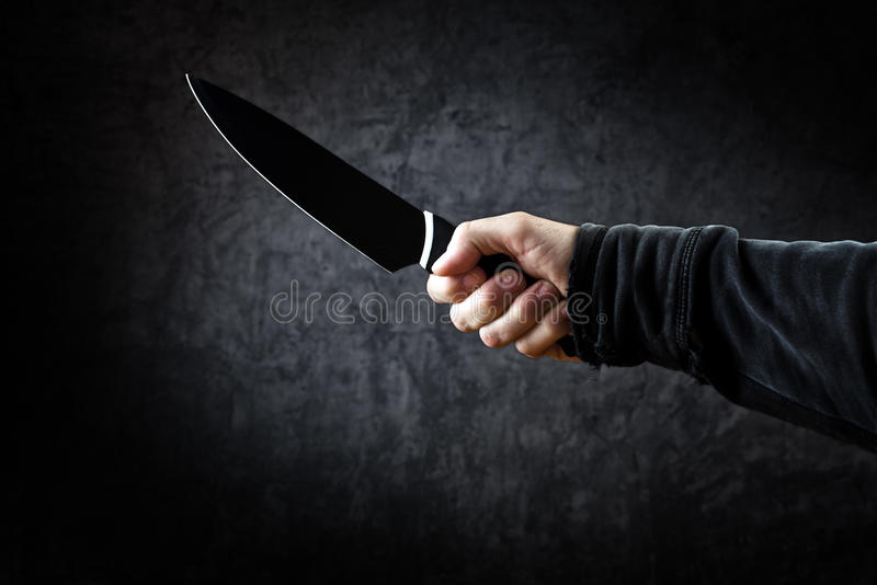 邪恶的人举行发光的刀子,在行动的凶手 免版税库存图片