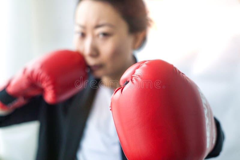 邪恶看照相机的西装和拳击手套的坚强和独立女实业家 库存照片