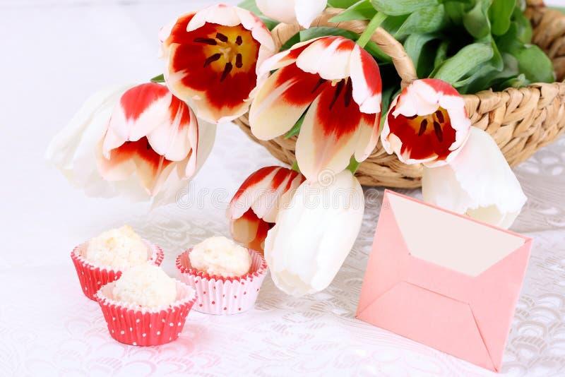 郁金香、曲奇饼和在一张空白桌布的空插件 免版税库存照片