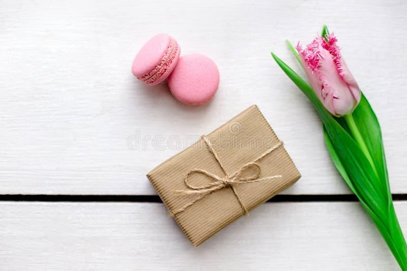 郁金香、礼物盒和蛋白杏仁饼干木白色背景 库存图片