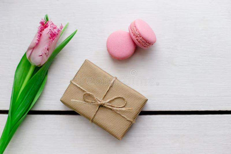 郁金香、礼物盒和蛋白杏仁饼干木白色背景 库存照片