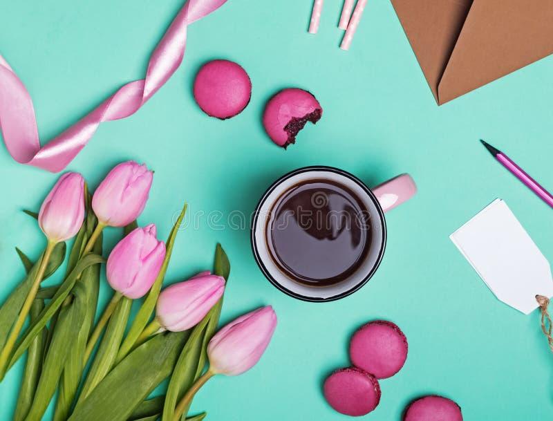 郁金香、macarons、丝带和咖啡在桃红色杯子 免版税图库摄影