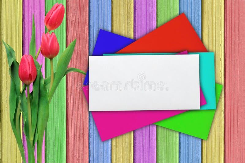 郁金香和五颜六色包围在破旧的油漆木桌 免版税图库摄影