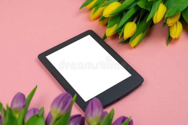 郁金香和片剂有白色大模型屏幕的在桃红色背景 贺卡为复活节或妇女的天 免版税库存照片