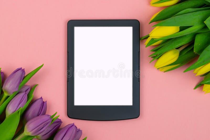郁金香和片剂有白色大模型屏幕的在桃红色背景 贺卡为复活节或妇女的天 免版税库存图片