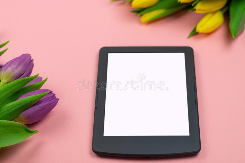 郁金香和片剂有白色大模型屏幕的在桃红色背景 贺卡为复活节或妇女的天 库存图片