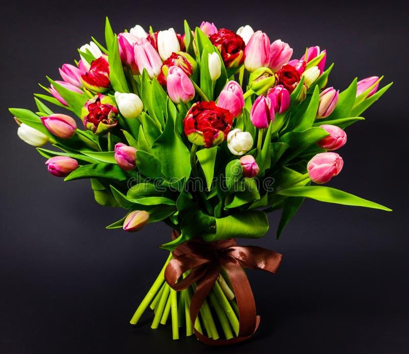 郁金香明亮的花束在黑暗的背景的有花卉背景 库存照片