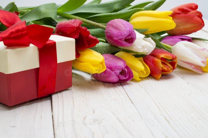 郁金香花束与一件礼物的在土气木板 库存图片