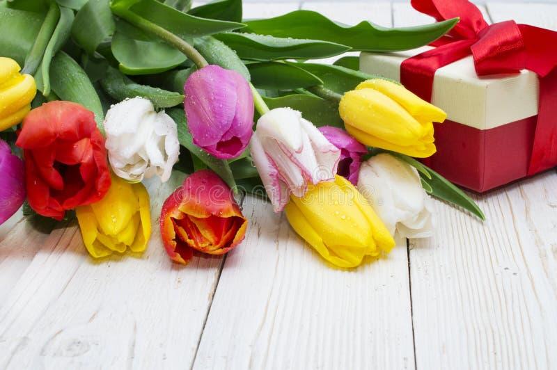 郁金香花束与一件礼物的在土气木板 免版税库存照片