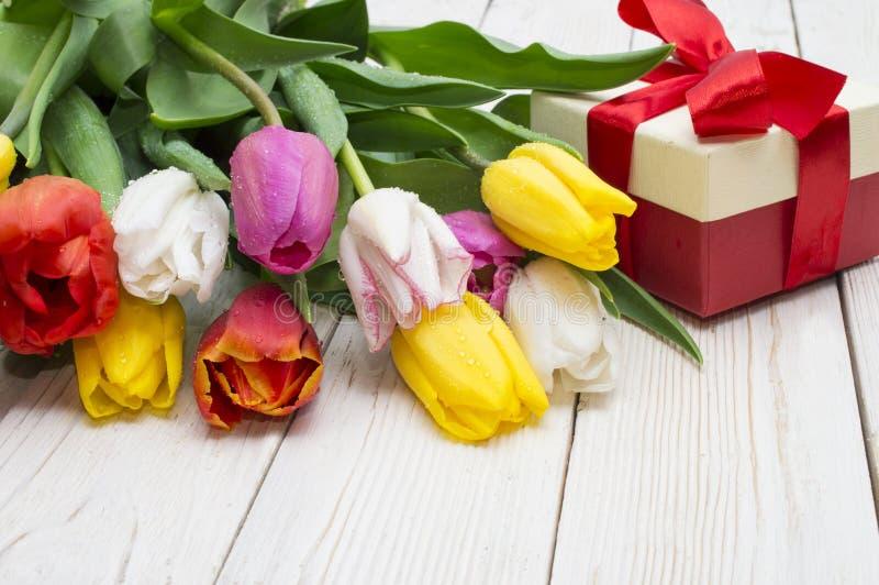 郁金香花束与一件礼物的在土气木板 图库摄影