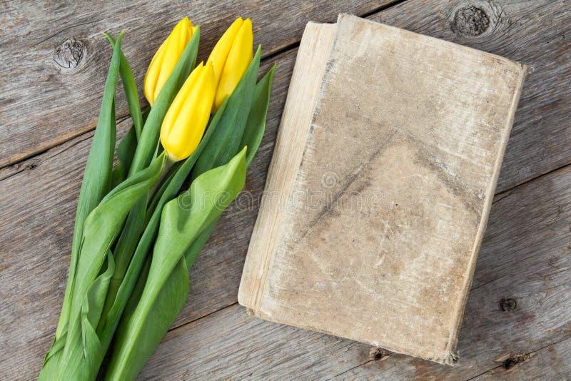 郁金香花束与旧书的 免版税库存照片