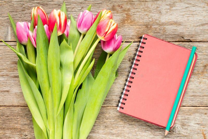郁金香花束和螺纹笔记本 图库摄影