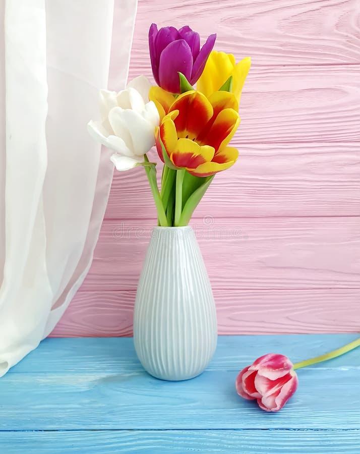 郁金香花束在一次花瓶问候设计绽放季节性美好的庆祝的在木背景 免版税库存图片