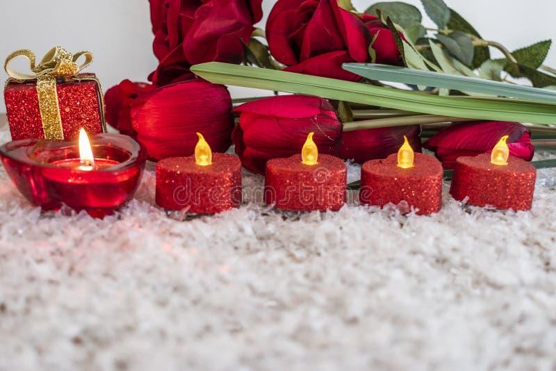 郁金香,玫瑰开花和在雪的心形的蜡烛象背景 免版税图库摄影