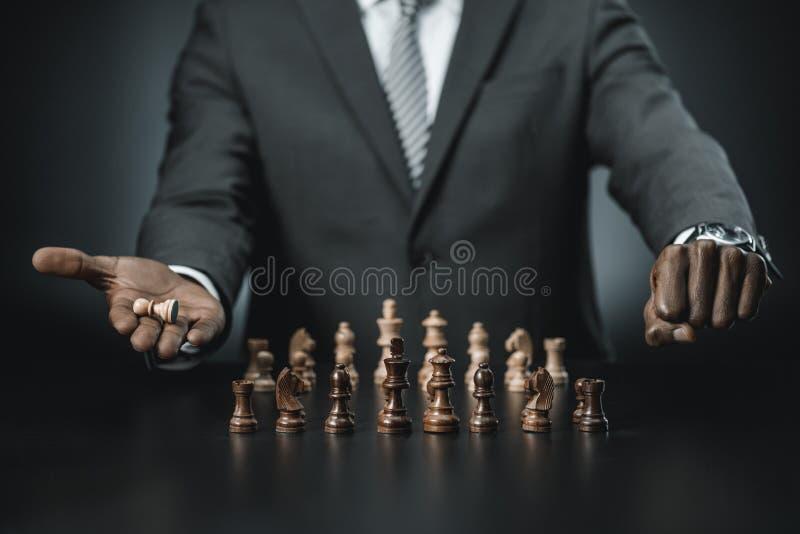 部份观点的与棋的非裔美国人的商人在手中计算 库存照片