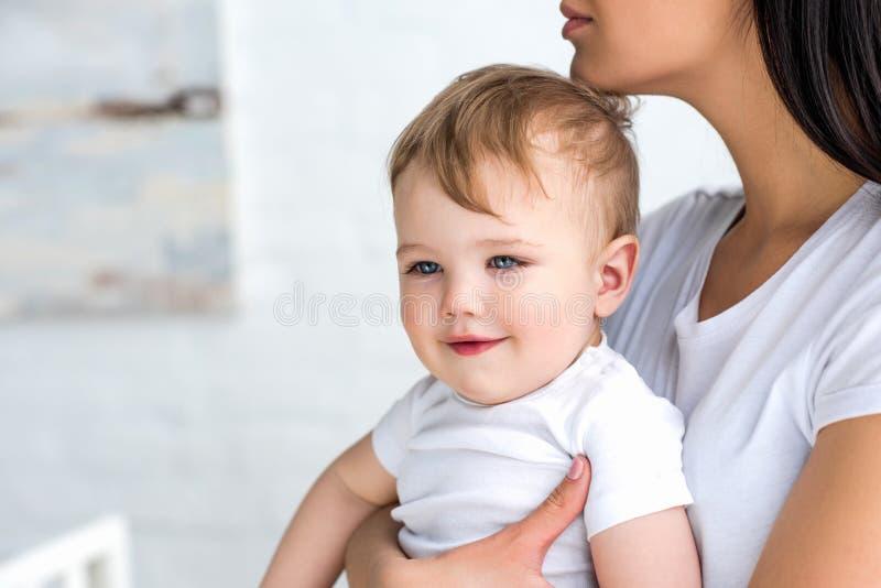 部份观点的有逗人喜爱的矮小的婴孩的母亲在手上 库存照片