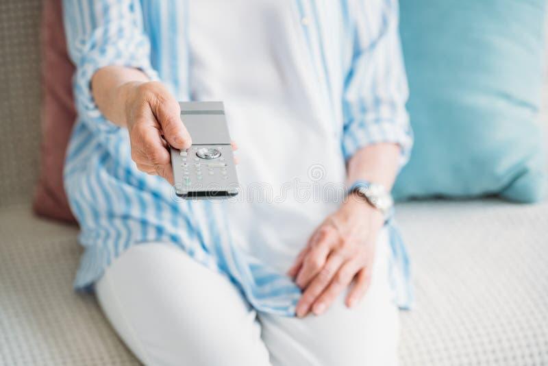 部份观点的有遥控观看的电视的资深妇女在沙发在家 免版税图库摄影