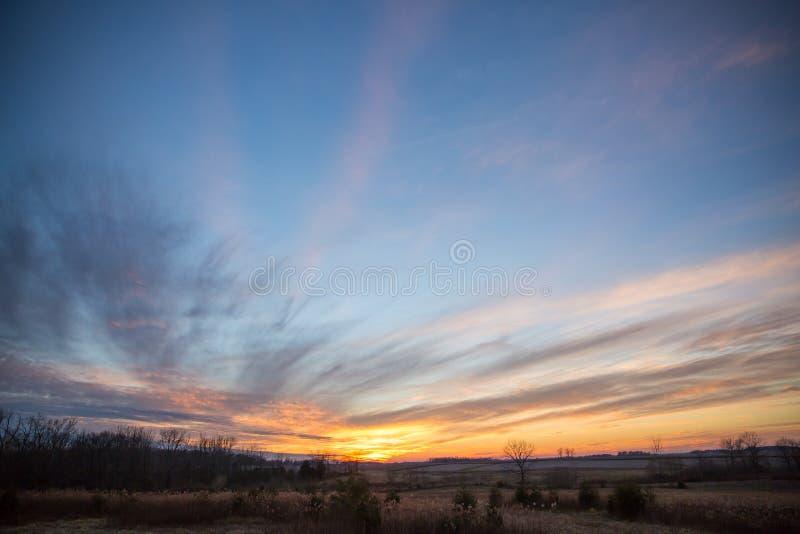 部分地在冬天领域和蜂蜜酒的多云剧烈的日落天空 库存照片