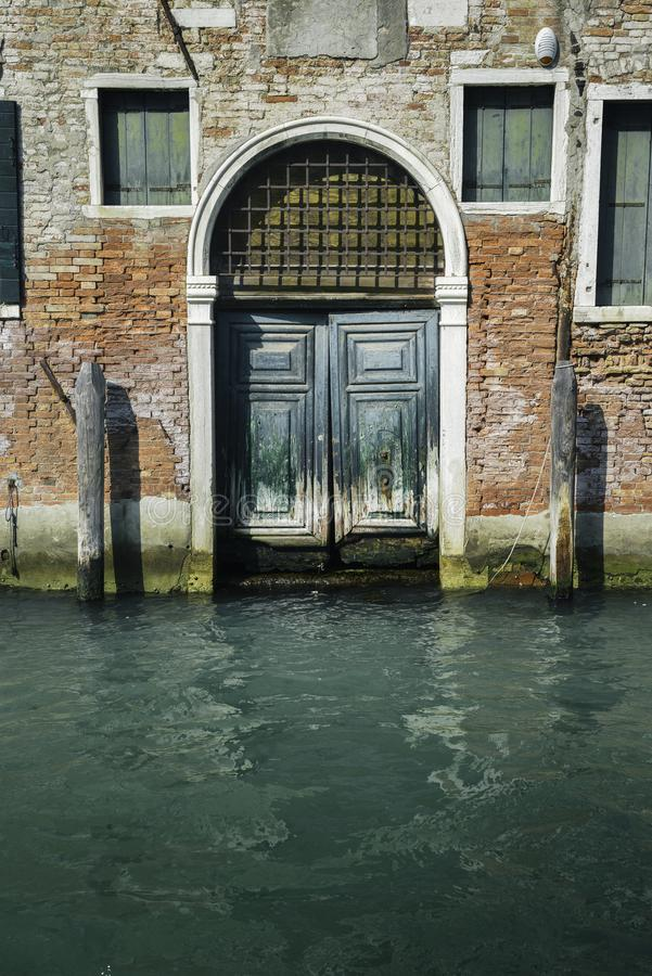 部分地有木葡萄酒门的生苔老砖房子门面  库存图片