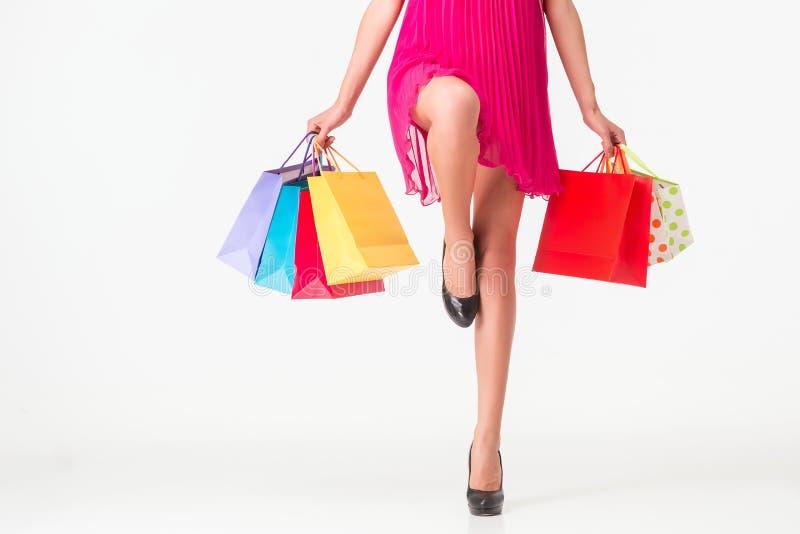 部分身体,美好的女性苗条腿 拿着纸购物袋的性感的女孩,隔绝在白色背景 免版税库存照片