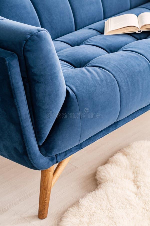 部分A长沙发的特写镜头在客厅内部的豪华藏青色挂毯穿戴了 在沙发的一本开放书 实际照片 免版税库存照片