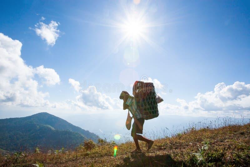 部落拉祜人运载在柳条筐的重的齿轮的远足者的 库存图片