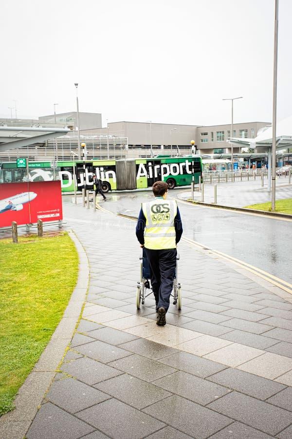 都伯林机场推挤残疾乘客的成员职员轮椅对机场主楼在夏天雨天,都柏林机场, 14 免版税图库摄影