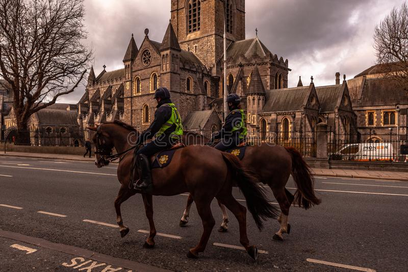 都伯林,爱尔兰–2019年3月 近拥挤控制马的警察到基督教会座堂在都伯林,爱尔兰 免版税库存图片