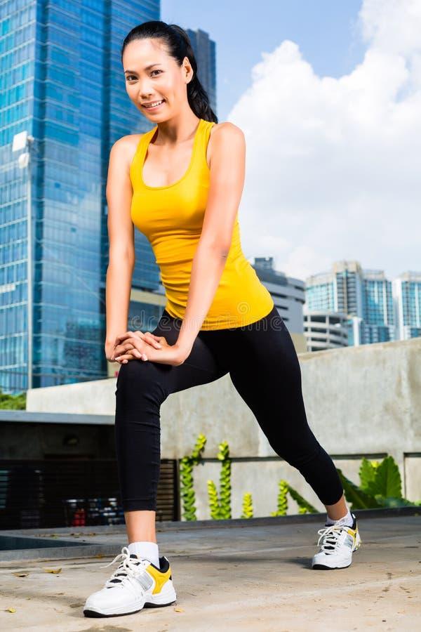 都市妇女在亚洲城市炫耀-健身 免版税库存图片