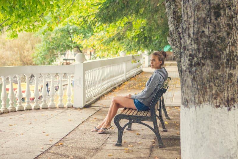 都市妇女坐公园和呼吸的深新鲜空气的长凳 免版税库存照片