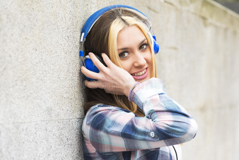 都市有耳机听的音乐的画象美丽的女孩 免版税库存照片