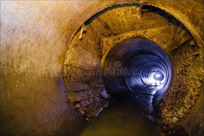 都市污水流动的投掷圆的下水道隧道管子 免版税图库摄影