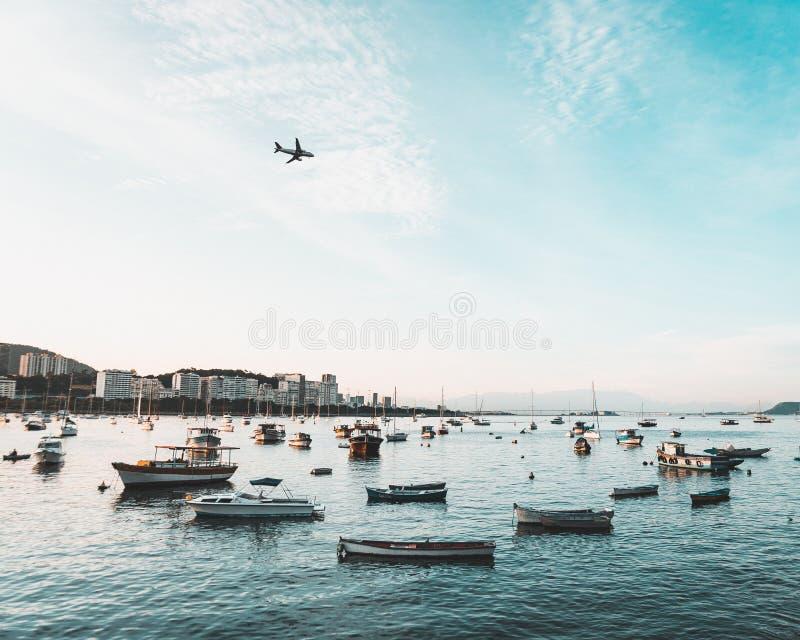 都市海滨城市的海岸美丽的射击有许多小船和一次飞机飞行的在天空 免版税库存图片