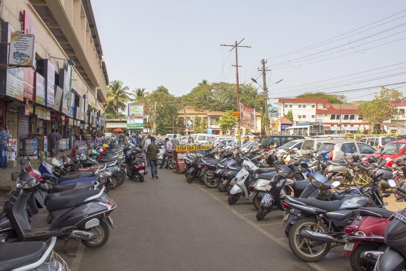都市现代房子和绿色背景的印度摩托车停车处和走人民  免版税库存照片