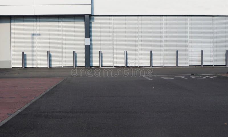 都市的背景 街道的交叉点在一个现代白色大厦前面的与金属街道杆行  免版税库存照片