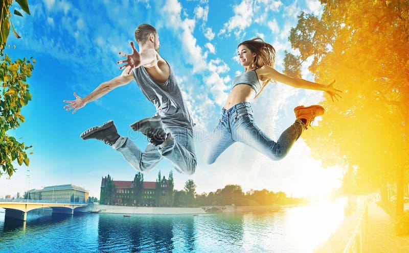 都市背景的两位跳跃的舞蹈家 免版税库存照片