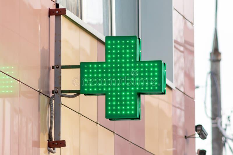 都市药房或药店看看标志,带领了在墙壁上的显示绿色十字架在城市街道 库存照片