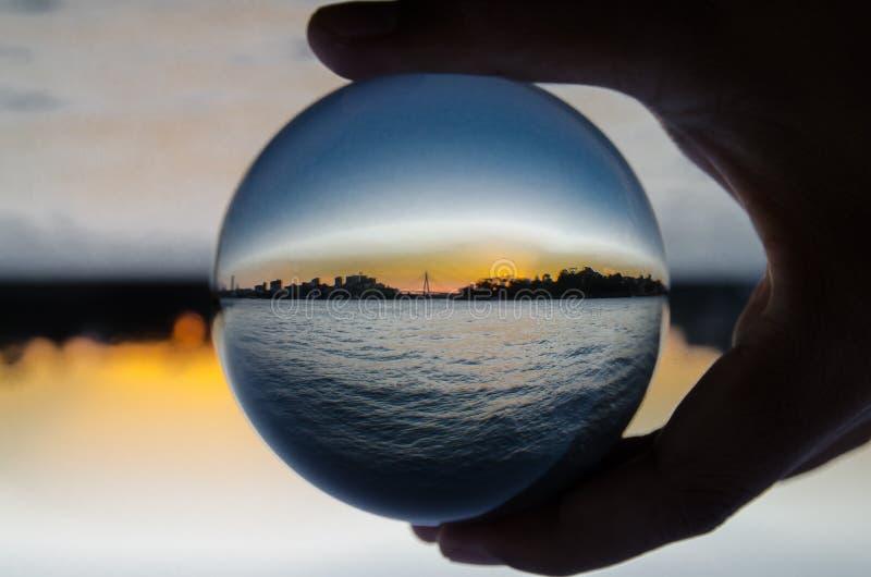 都市风景剪影与黑暗的海景摄影的在清楚的水晶玻璃球 图库摄影