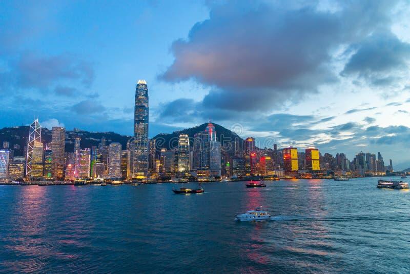 都市风景和地平线在维多利亚港口暮色时间的 普及的见解问题的日落时间的香港市 库存照片