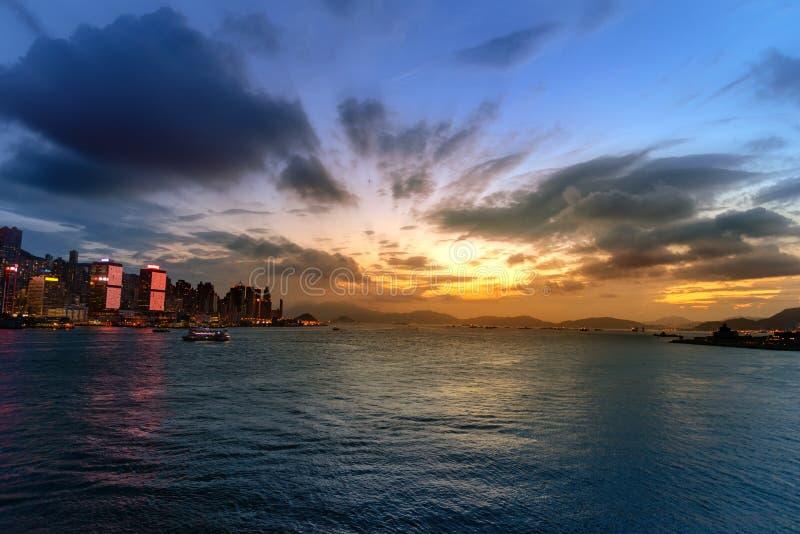 都市风景和地平线在维多利亚港口暮色时间的 普及的见解问题的日落时间的香港市 免版税库存照片